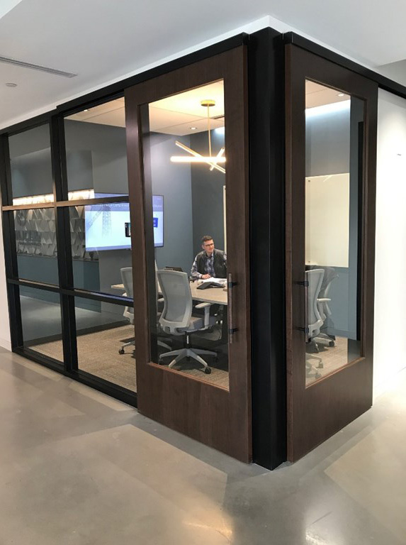 Corner office with custom walnut sliding door supplied by LaForce Inc.