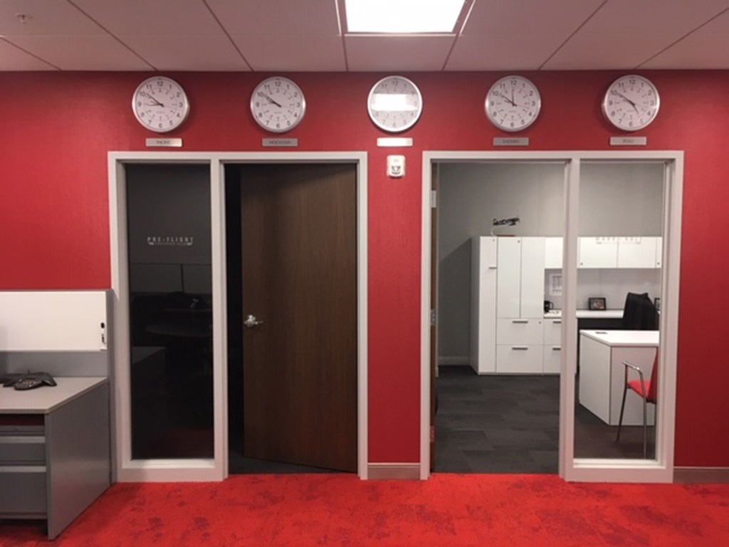 Office space with red painted walls and carpet and two walnut wood door and hollow metal frames supplied by LaForce Inc.